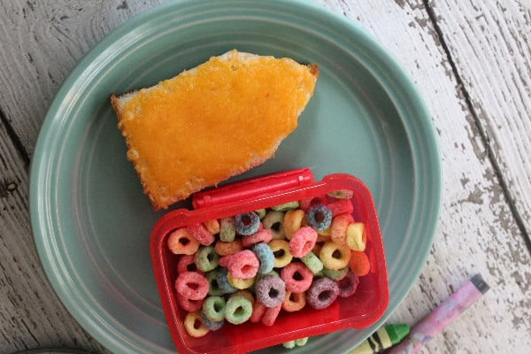 crayon shaped cheese toast on a teal plate with fruit loops in a container to use for the day the crayons quit unit study
