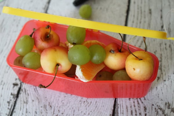 cherries, oranges, and grapes in a crayon shaped container as a snack idea for the day the crayons quit unit study